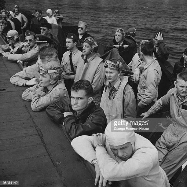 View of American servicemen as they watch planes land on the deck of an aircraft carrier during World War II 1943 '
