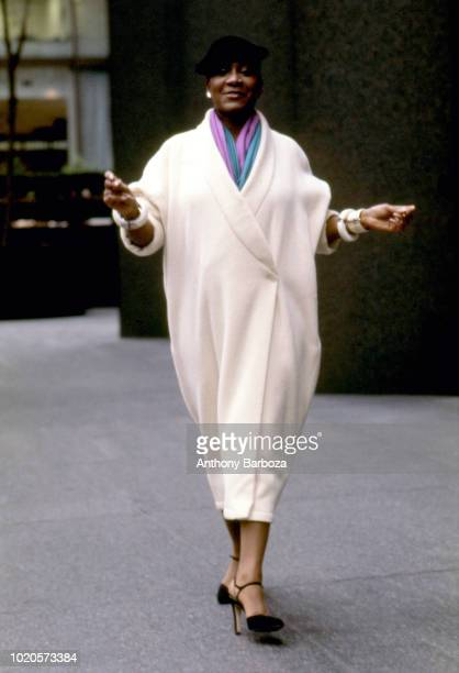 View of American singer and actress Patti LaBelle dressed in a long white coat as she walks on the sidewalk and snaps her fingers 1980s