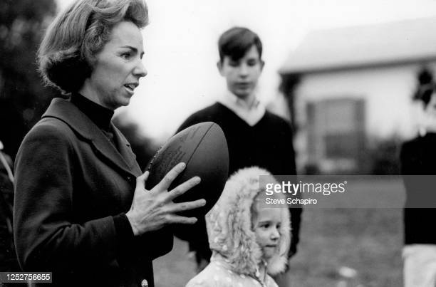 View of American socialite Ethel Kennedy holds a football during a game with a group of kids on the grounds of her home Hickory Hill McLean Virginia...