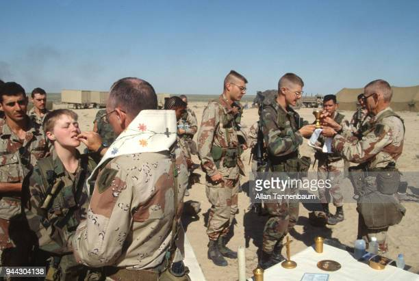 View of American soldiers as they receive communion from military chaplains during the Gulf War Iraq 1991