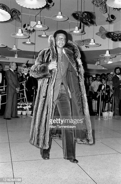 View of American tennis player Arthur Ashe , dressed in a fur coat, on the catwalk during a men's fur fashion show at the Market Bar, New York, New...