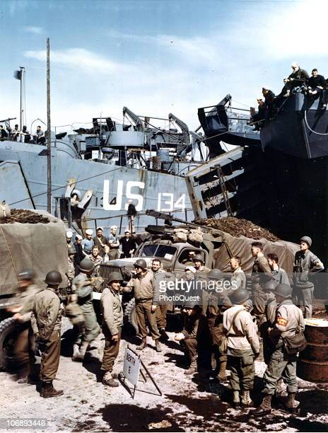 View of American trucks as they are loaded onto an unidentified LST as a number of soldiers stand by Weymouth England early June 1944 The men are in...