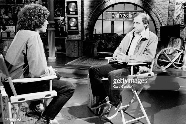 View of American VJ Mark Goodman and English Rock and Blues musician Mark Knopfler as they sit in director chairs during an interview at MTV Studios...