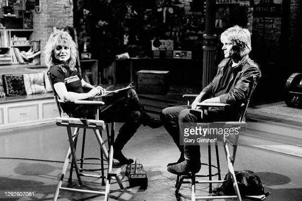 View of American VJ Nina Blackwood and Canadian Rock musician Bryan Adams as they sit in director's chairs during an interview at MTV Studios, New...