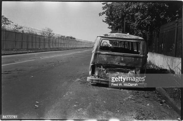 View of an abandoned and apparently burnt vehicle on the side of an unspecified road New York October 6 1982