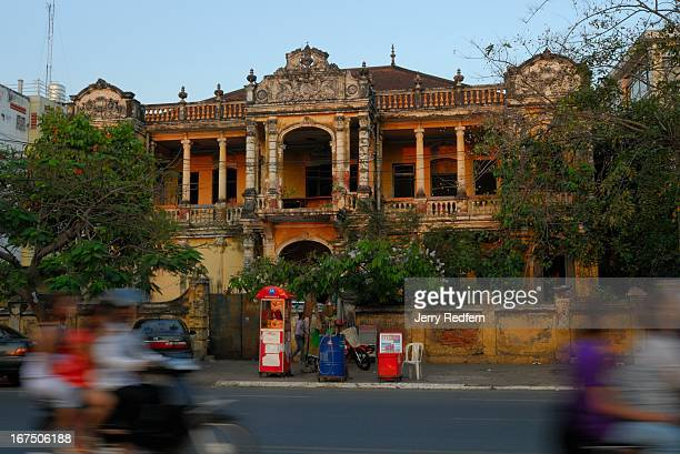View of an abandoned French colonial-era mansion across the street from the National Museum in Phnom Penh. The dilapidated building's lucrative...
