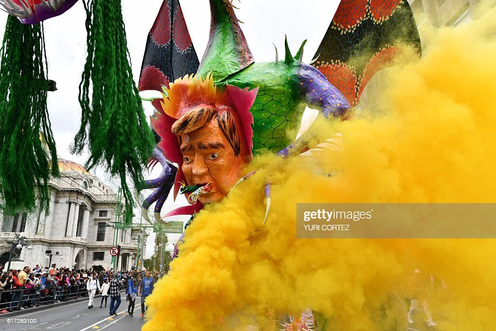 View of an 'Alebrije' -Mexican folk art traditional sculptures representing fantastical creatures - with a figure representing US Republican presidential nominee Donald Trump during the tenth Monumental 'Alebrijes' Parade and contest organized by the Folk Art Museum, on October 22, 2016 in Mexico City. More than two hundreds 'Alebrijes' take part in the event. / AFP / YURI
