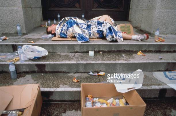 View of an amateur runner lying in a doorway covered with an ADT branded space blanket after completing the ADT London Marathon circa 1990