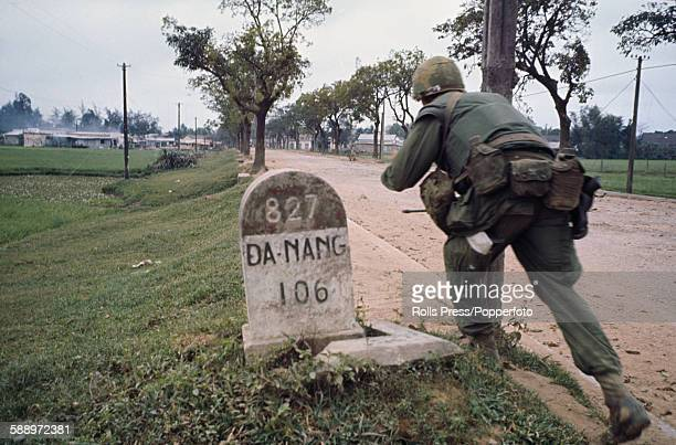 View of an American soldier running along a street on the outskirts of the Vietnamese City of Hue during the Battle of Hue part of the Tet Offensive...