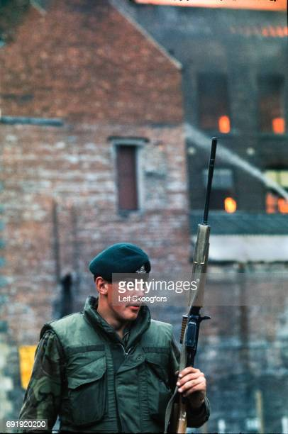 View of an armed British soldier on patrol as behind him an unspecified building burns Belfast Northern Ireland June 1974