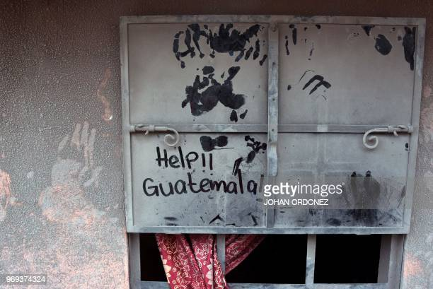 View of an ashcovered window reading Help Guatemala in the village of San Miguel Los Lotes which was also flooded with hot mud that descended from...