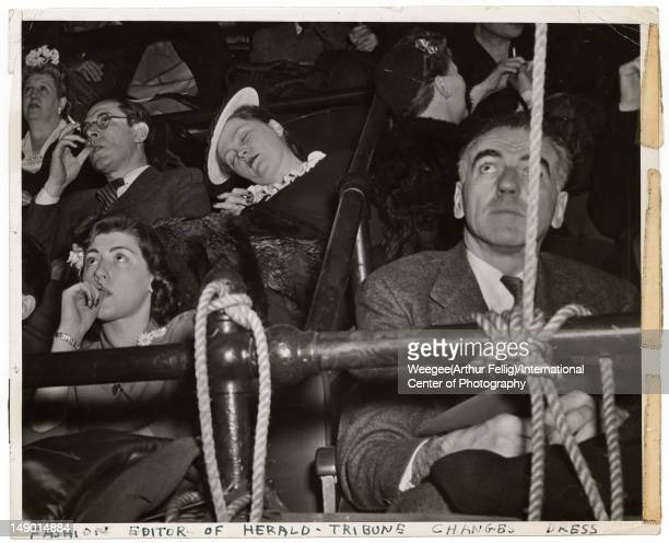 View of an audience which includes a sleeping woman with her head slumped over onto her shoulder 1943 The text at the bottom reads 'Fashion Editor of...
