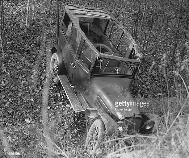View of an automobile accident showing a car with its roof ripped off and a damaged window while facing steeply down a hill early twentieth century