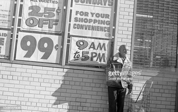View of an elderly man as he leans against the exterior wall of a supermarket in Queens New York New York September 1980