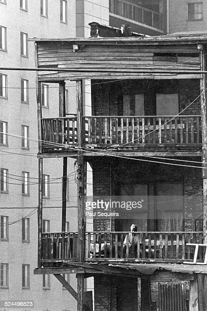 View of an elderly man sitting in a backyard deck or porch in a south side tenement building Chicago Illinois 1960s
