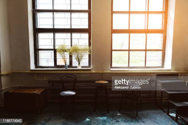 view of an empty room with different antique chairs large panoramic window against a white brick wall. stylish loft interior of the studio. - ベージュ ストックフォトと画像