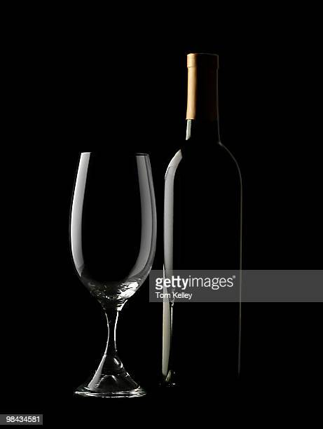 View of an empty wine glass and an uncorked bottle seen illuminated from the side against a black background 2009