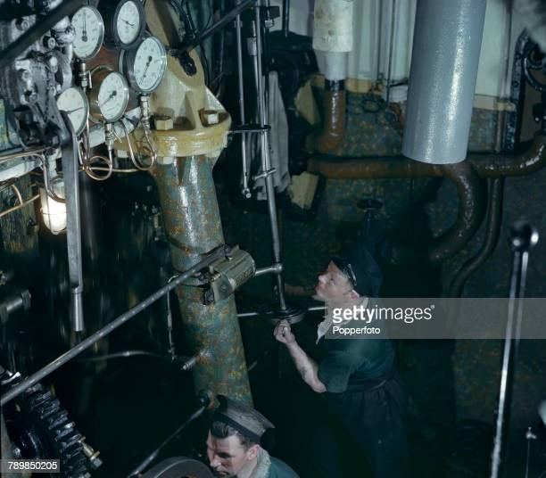 View of an engineer increasing speed inside the engine room of a Royal Navy converted trawler on convoy patrol in the North Sea in March 1943 The...