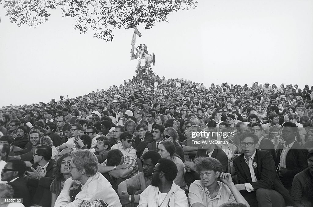 View of an enormous crowd of demonstrators as they sit on a hill that leads up to a statue of Union General John A. Logan astride a horse in Grant Park during protests at Democratic National Convention, Chicago, Illinois, August 27, 1968.
