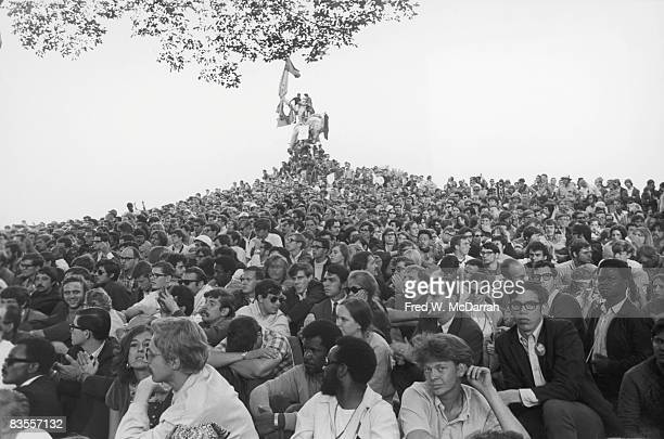 View of an enormous crowd of demonstrators as they sit on a hill that leads up to a statue of Union General John A Logan astride a horse in Grant...