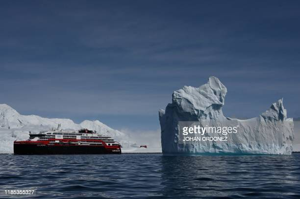 View of an iceberg and the Hurtigruten hybrid expedition cruise ship MS Roald Amundsen on Half Moon island, Antarctica on November 09, 2019.