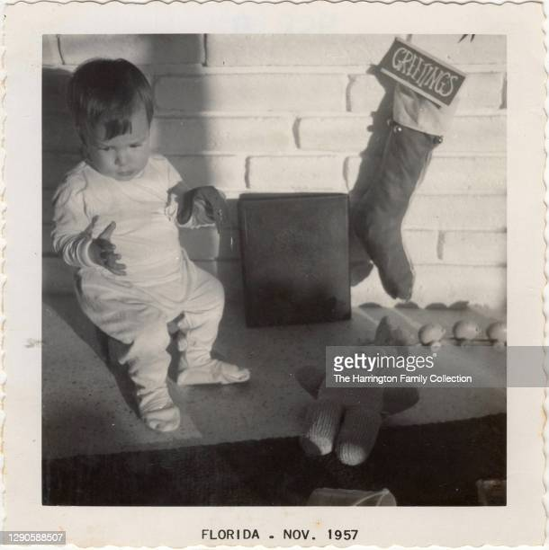 View of an infant seated on a mantle beside several toys and a Christmas stocking, Florida, December 25, 1957.