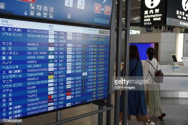 View of an information sign board showing the cancellation of all the international flights at the Chubu Centrair International Airport Japan expands...