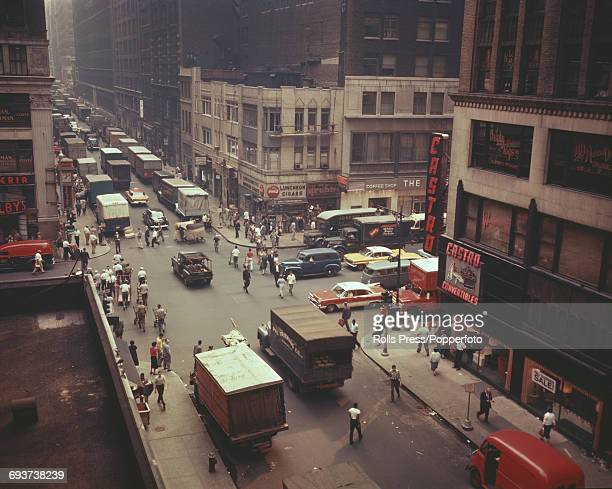 View of an intersection of street and avenue in midtown Manhattan New York with trucks cars and pedestrians crossing in rush hour circa 1966
