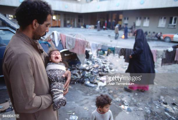 View of an Iraqi man as he holds his crying baby at a refugee camp during the Gulf War Iraq 1991
