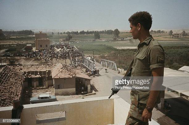 View of an Israeli soldier on a roof top on the West Bank territory observing Arab refugees crossing over the River Jordan via the wrecked Allenby or...