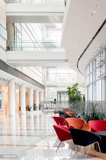 view of an office building lobby with colorful chairs - hotel lobby stock pictures, royalty-free photos & images