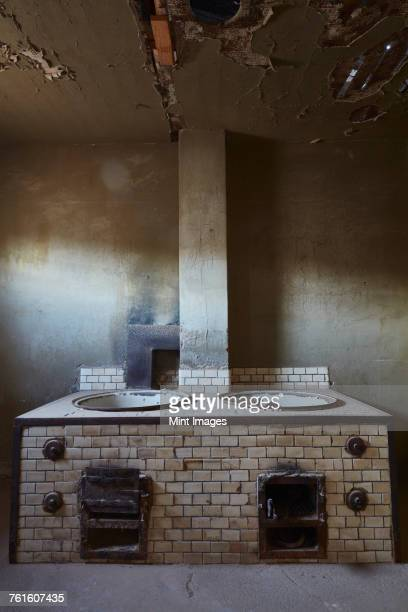 A view of an old fashioned stove in a derelict building.