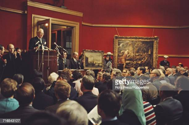 View of an Old Masters sale under way with the auctioneer taking bids in Christie's auction house in London in June 1971 Hanging on the wall behind...