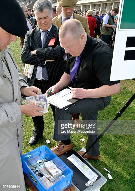 View of an oncourse bookmaker taking bets from a punter on Ladies Day during the 2012 Cheltenham National Hunt Festival at Cheltenham racecourse in...