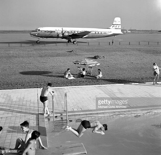 A view of an Pan American Airways DC4 Clipper airplane on the tarmac as people swim in a swimming pool at the Ezeiza Airport in Buenos Aires Argentina