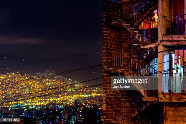 View of an unfinished threestory apartment house in the Pablo Escobar neighborhood during the night in front of the city lights of Medellín Colombia...