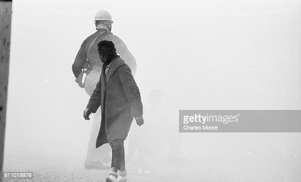 View of an unidentified Civil Rights marcher and a police officer in a gas mask in a cloud of tear gas at the base of the Edmund Pettus Bridge during...