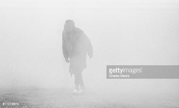 View of an unidentified Civil Rights marcher in a cloud of tear gas at the base of the Edmund Pettus Bridge during the first Selma to Montgomery...