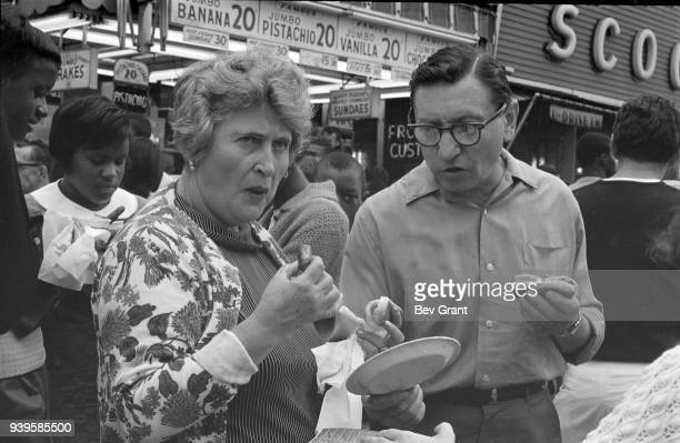 View of an unidentified couple as they eat hot dogs in front of Nathan's Famous fast food restaurant at Coney Island Brooklyn New York New York July...