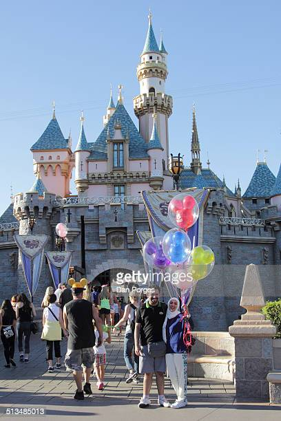 View of an unidentified couple as they pose with Mickey Mouse balloons in front of the Sleeping Beauty Castle at the Disneyland amusement park...