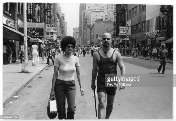 View of an unidentified couple as they walk along 8th Street in Greenwich Village New York New York August 8 1970