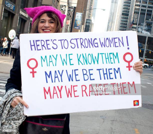 View of an unidentified demonstrator at the Women's March on New York New York January 20 2018 She holds a sign that reads 'Here's to Strong Women...