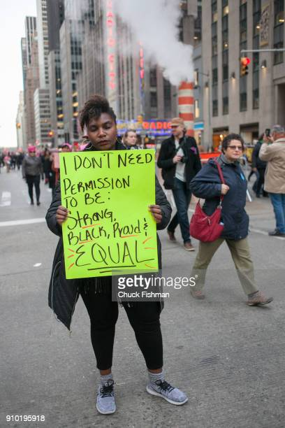 View of an unidentified demonstrator on Sixth Avenue during the Women's March on New York New York New York January 20 2018 She holds a sign that...