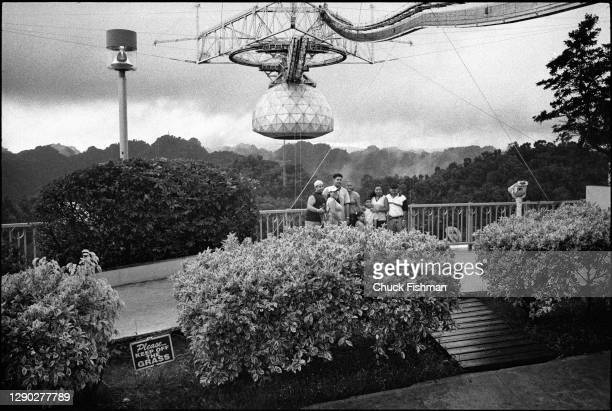 View of an unidentified group of people as they pose for a photograph on an observation deck overlooking the radio telescope at the Arecibo...