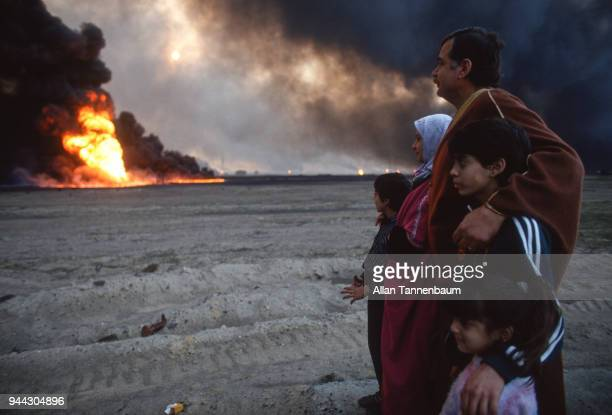 View of an unidentified Kuwaiti family as they watch oil wells burn in front of them Kuwait 1991