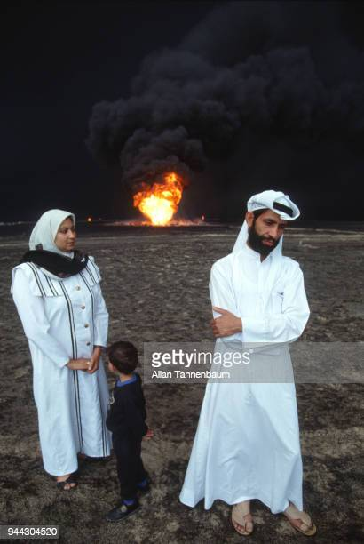 View of an unidentified Kuwaiti family while an oil well burns behind them Kuwait 1991