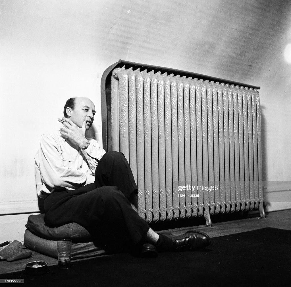 View of an unidentified man, a photographer, sitting next to a radiator located in an attic, and smoking a cigarette, New York, 1948.