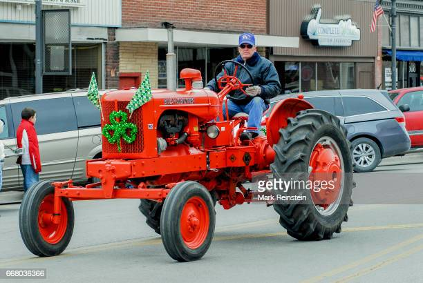View of an unidentified man as he drives a restored midcentury AllisChalmers 'WD' tractor during the the annual Saint Patrick's Day Parade Emporia...