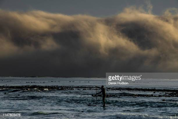 View of an unidentified man as he paddle boards through the surf off of Long Beach Kommetjie Western Cape South Africa May 1 2019 A wall of sea mist...