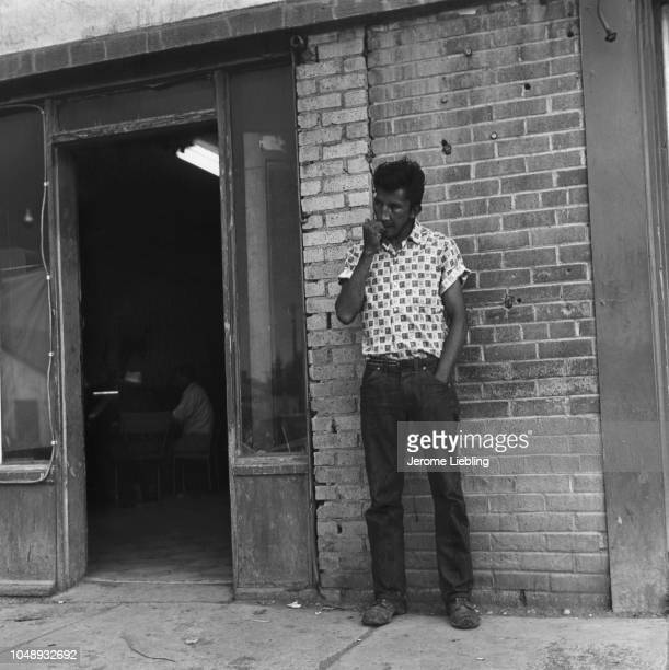 View of an unidentified man as he stands outside a store on the Blackfeet Indian Reservation Browning Montana 1964 Two other men are visible through...